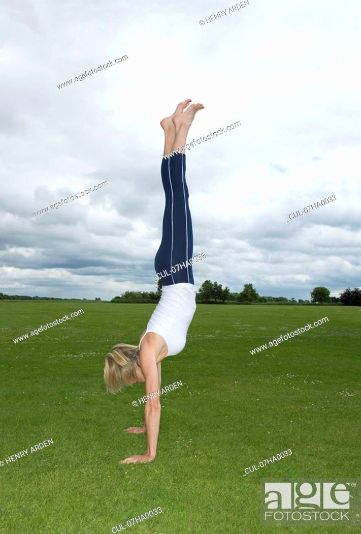 Stock Photo: Woman in park doing handstand.