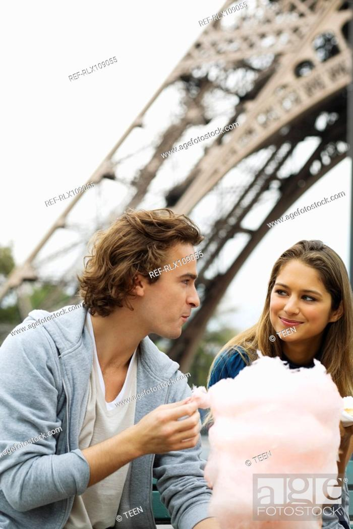 Stock Photo: Young couple in front of Eiffel tower man eating cotton candy, Paris, France.