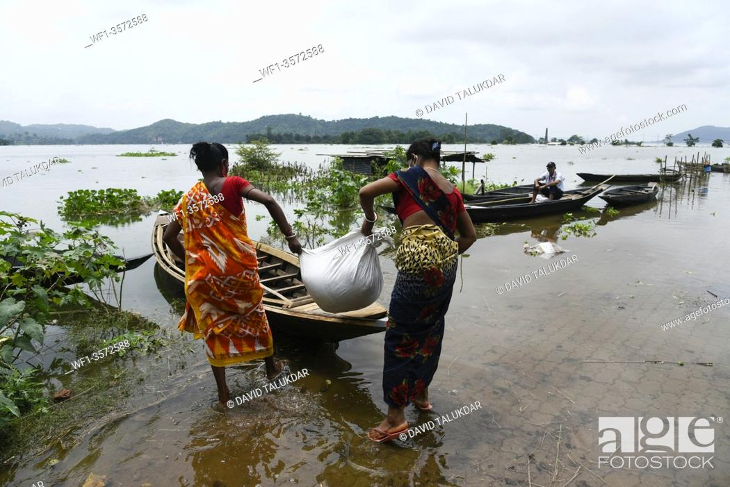 Stock Photo: Villagers waking wade through a flooded road, in Kamrup district of Assam, Monday, July 13, 2020.