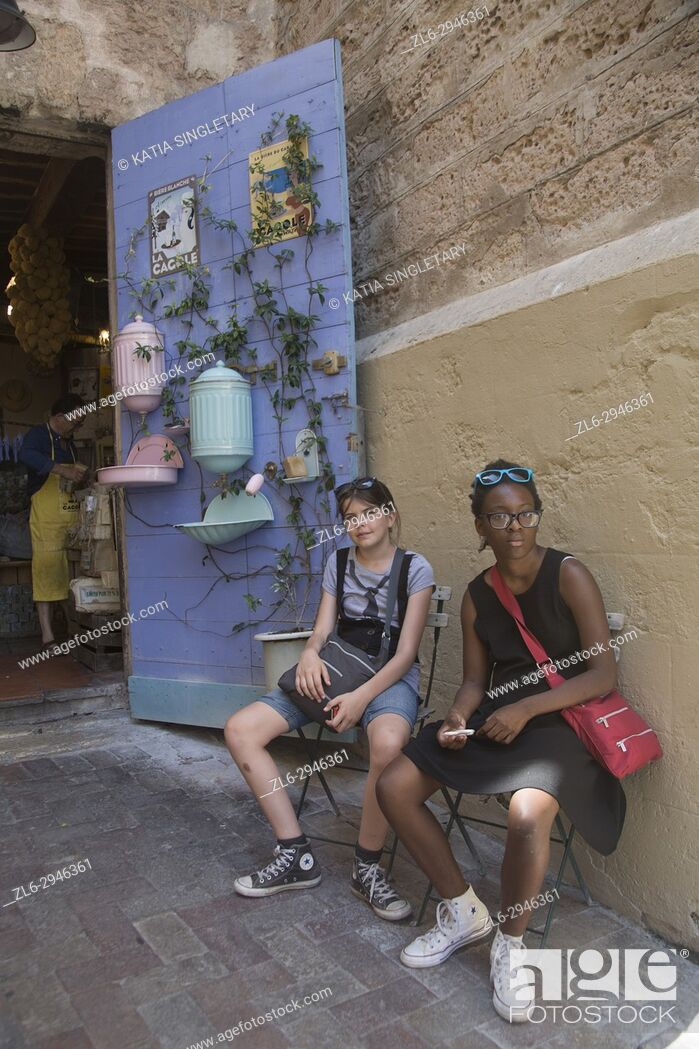 Stock Photo: Two teenage girls, one African American and one caucasian sitting, tired at the outside of a store front in the Quarter of Le Panier in Marseilles.