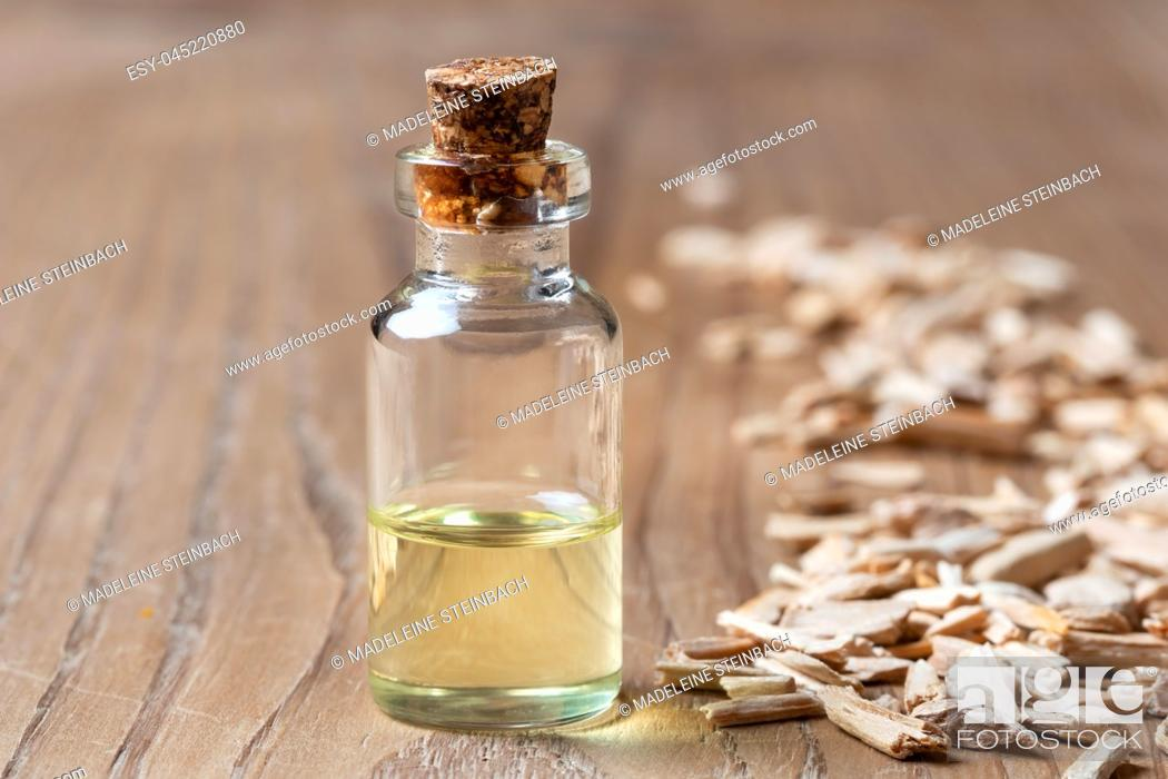 Stock Photo: A bottle of essential oil with cedar wood chips on a table.