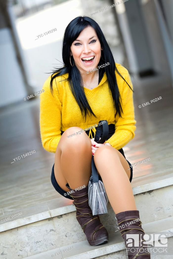 Stock Photo: Attractive young woman is sitting in the street laughing.