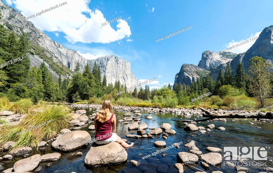 Imagen: Young woman sitting on stone in River Merced, Valley View, view of El Capitan, Yosemite National Park, California, USA.
