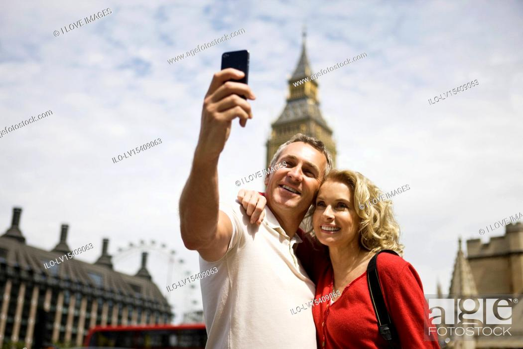 Stock Photo: A middle-aged couple standing at Parliament Square, taking a photograph.
