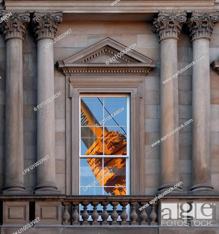 Stock Photo: Close up yellow crane reflected in window of 19c classical facade.