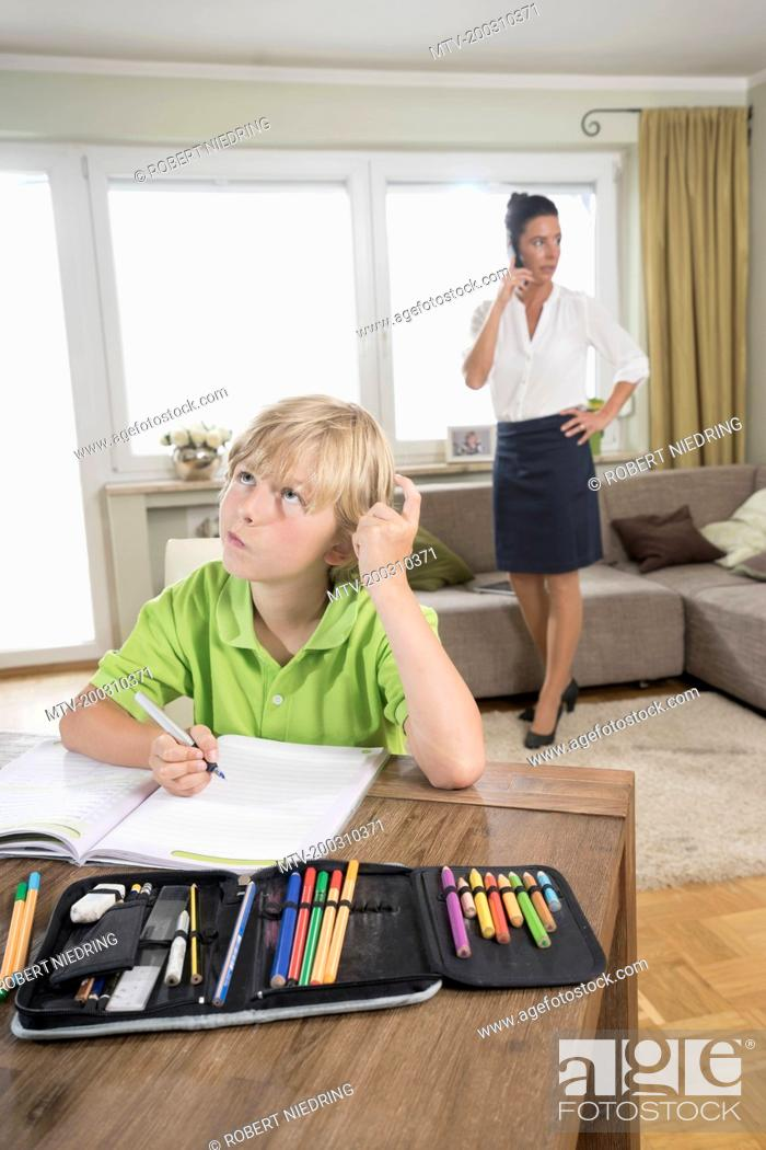 Stock Photo: Boy studying while mother has business call, Bavaria, Germany.