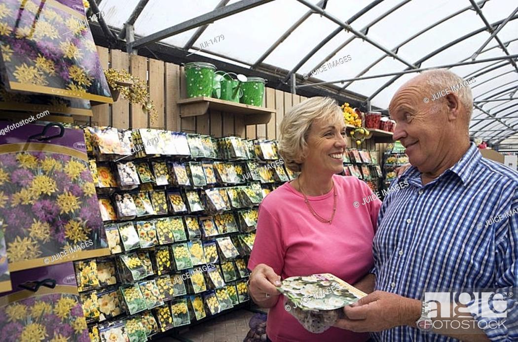 Stock Photo: Senior couple shopping in garden centre, holding pack of flower bulbs, smiling.