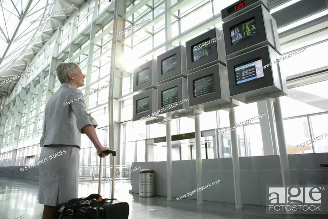 Stock Photo: Mature woman looking at departure screens at airport.