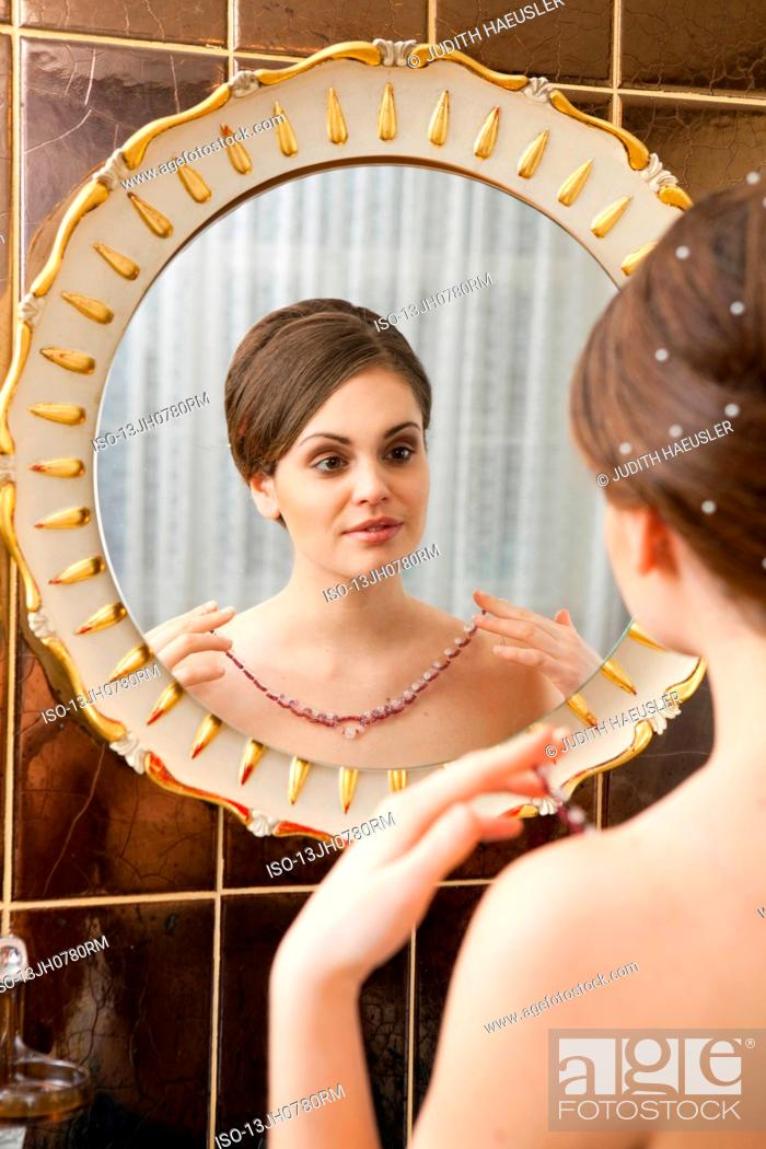 Stock Photo: woman with chain in front of mirror.