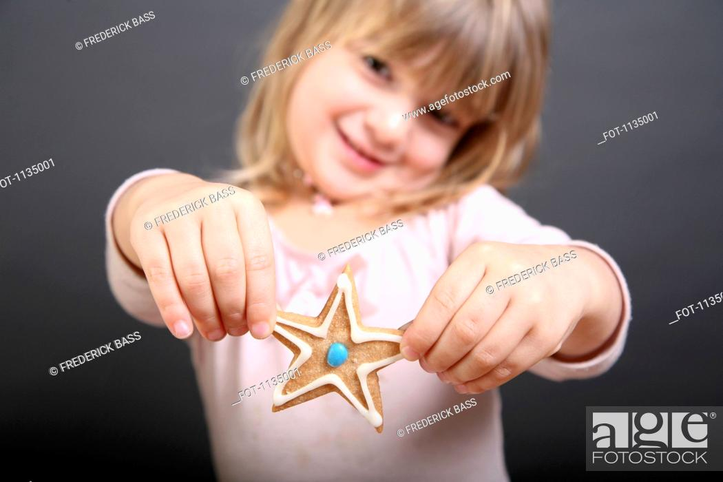 Stock Photo: A girl holding out up a star shaped Christmas cookie.