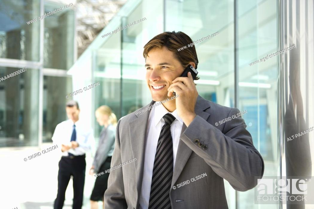 Stock Photo: Businessman using cell phone, smiling.