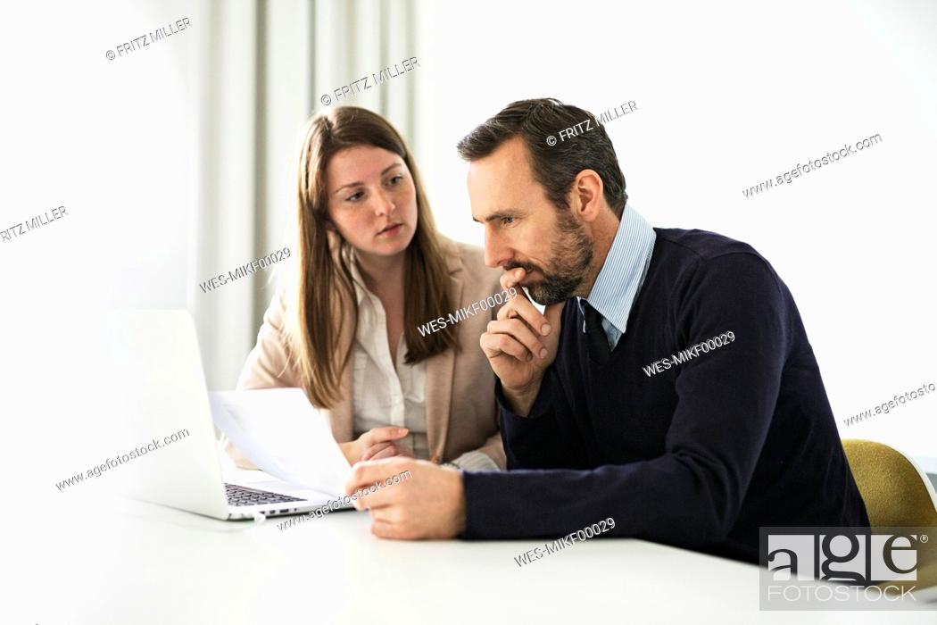 Stock Photo: Businessman and employee with laptop and documents working at desk in office.