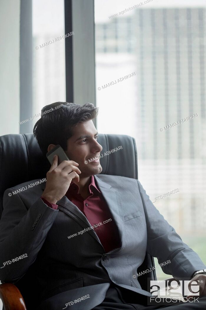 Stock Photo: India, Businessman in suit sitting in chair and using mobile phone.