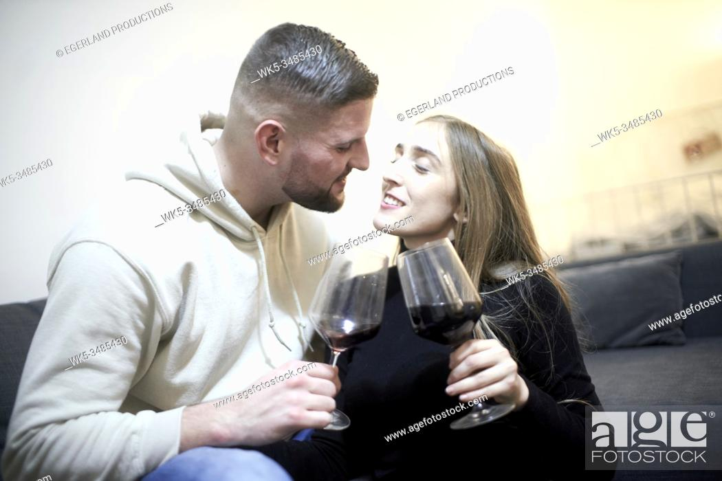 Stock Photo: couple with wine glasses on couch feeling inclination towards each other.