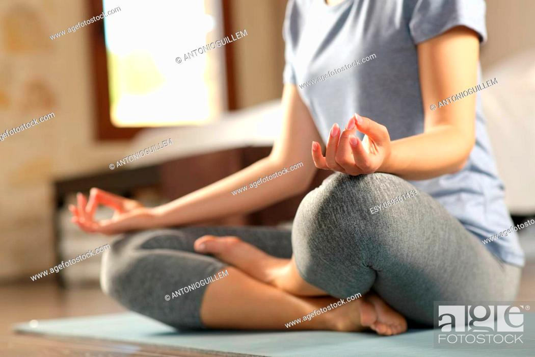 Stock Photo: Close up of a woman doing yoga exercise on the floor at home.
