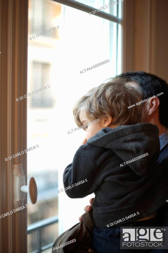 Stock Photo: Toddler boy in father's arms, looking out window.