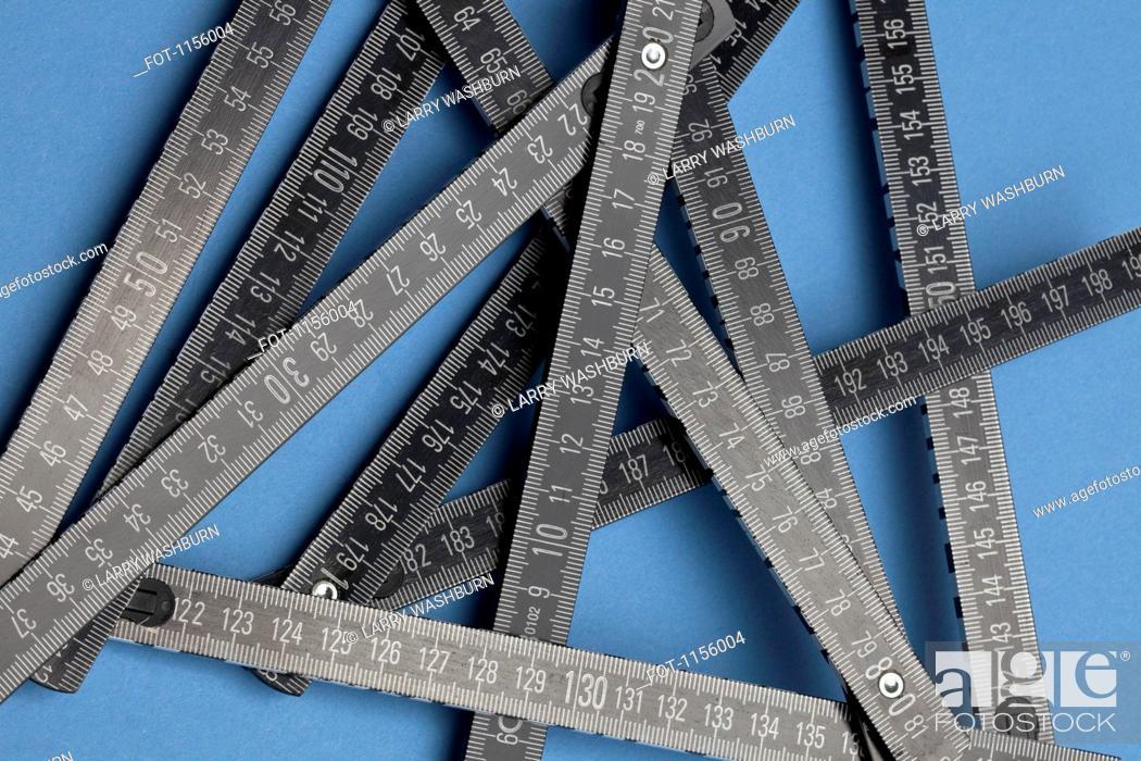 Stock Photo: A black folding ruler on a blue background.