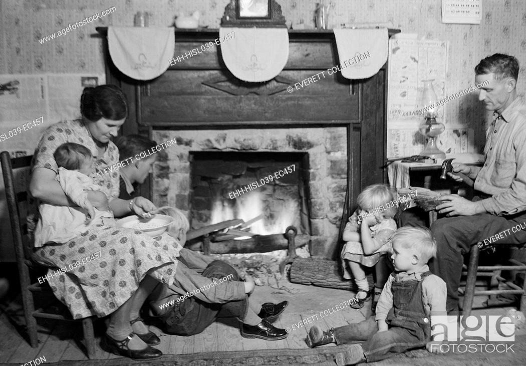 Stock Photo: Fletcher Carden is a night-watchman at the bunkhouses at TVA's Norris Dam. He repairs a shoe while sitting by the fireplace with his wife and family.
