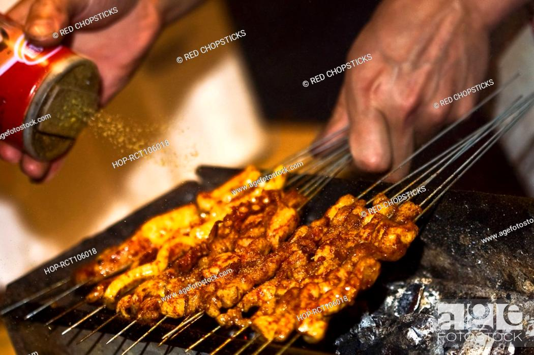Stock Photo: Close-up of a person's hand sprinkling spice on roasted food, Nanjing, Jiangsu Province, China.