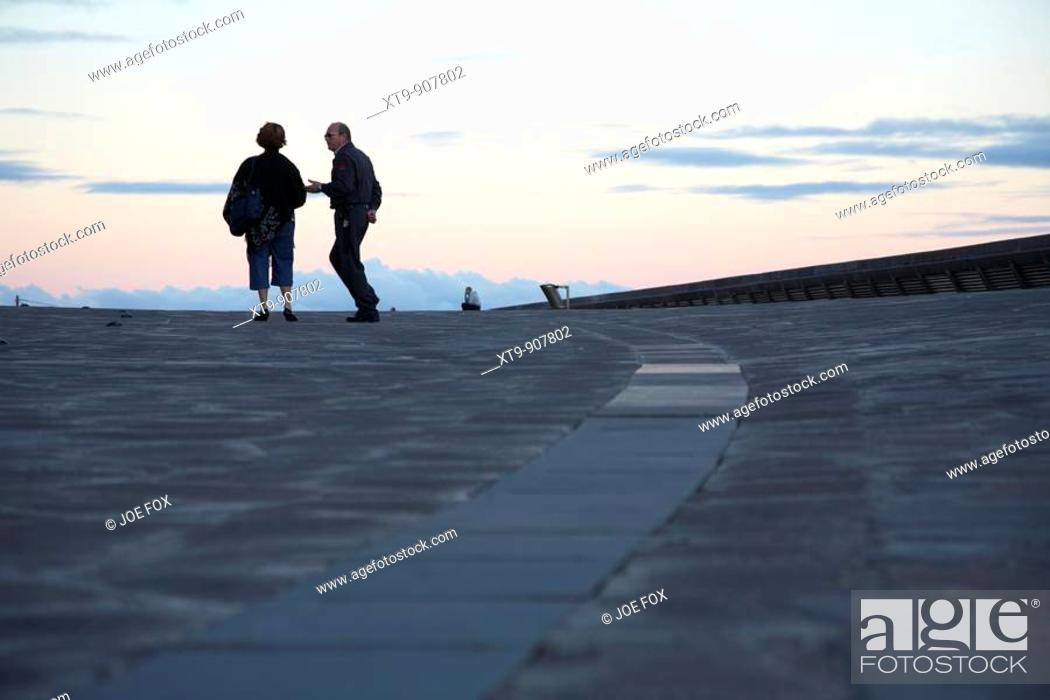 Stock Photo: single lone female with security guard talking with men in the distant background in santa cruz tenerife canary islands spain.