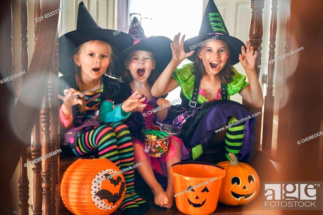 Stock Photo: Happy Halloween! Three cute little laughing girls in witches costumes.