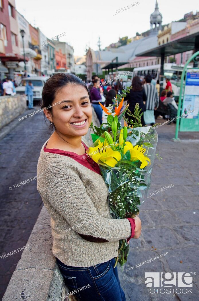 Imagen: Young woman holding a bouquet of flowers in the street; Guanajuato, Mexico.
