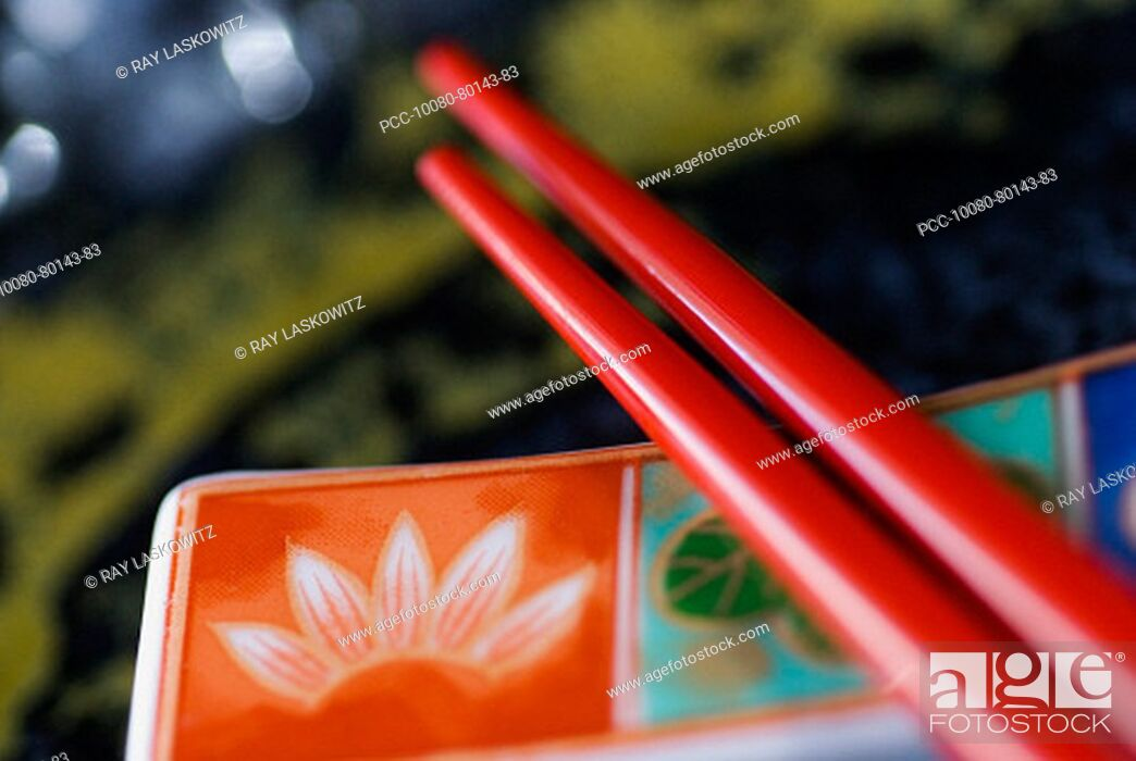 Stock Photo: Red chopsticks laid upon a colorful plate.