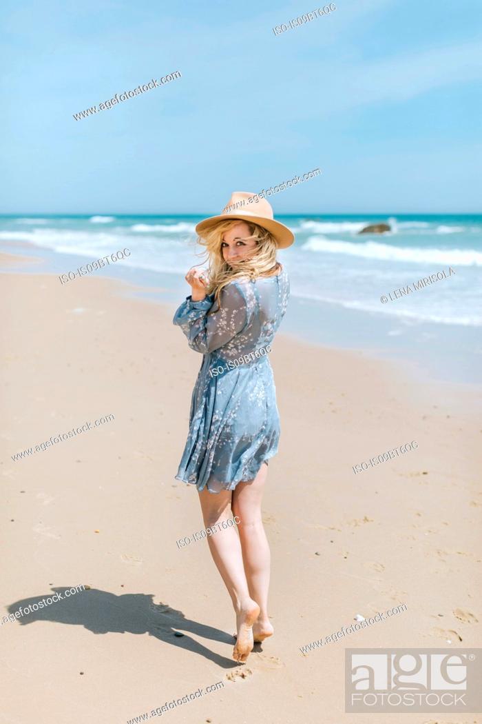 Stock Photo: Barefoot young woman on windy beach, portrait, Menemsha, Martha's Vineyard, Massachusetts, USA.