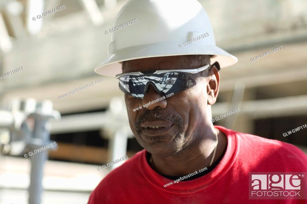 Stock Photo: Close-up of a male construction worker with a hardhat and a pair of sunglasses.