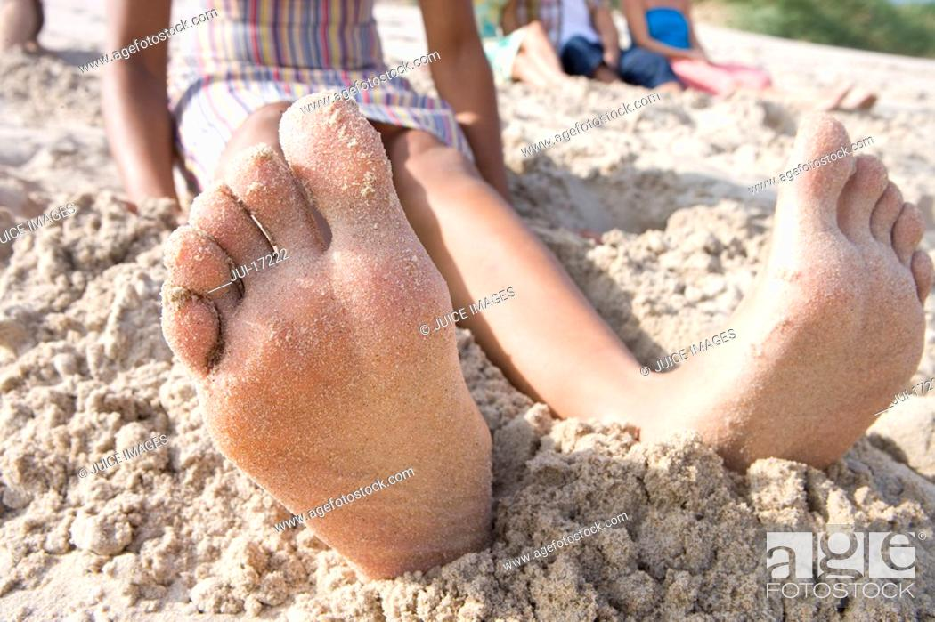 Stock Photo: Close-up of woman's barefeet in sand at beach.