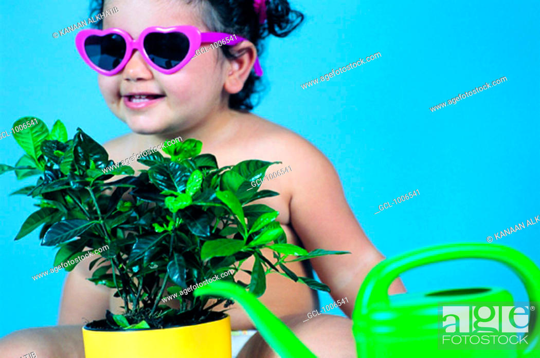 Stock Photo: Toddler wearing sunglasses with indoor plant and watering can.