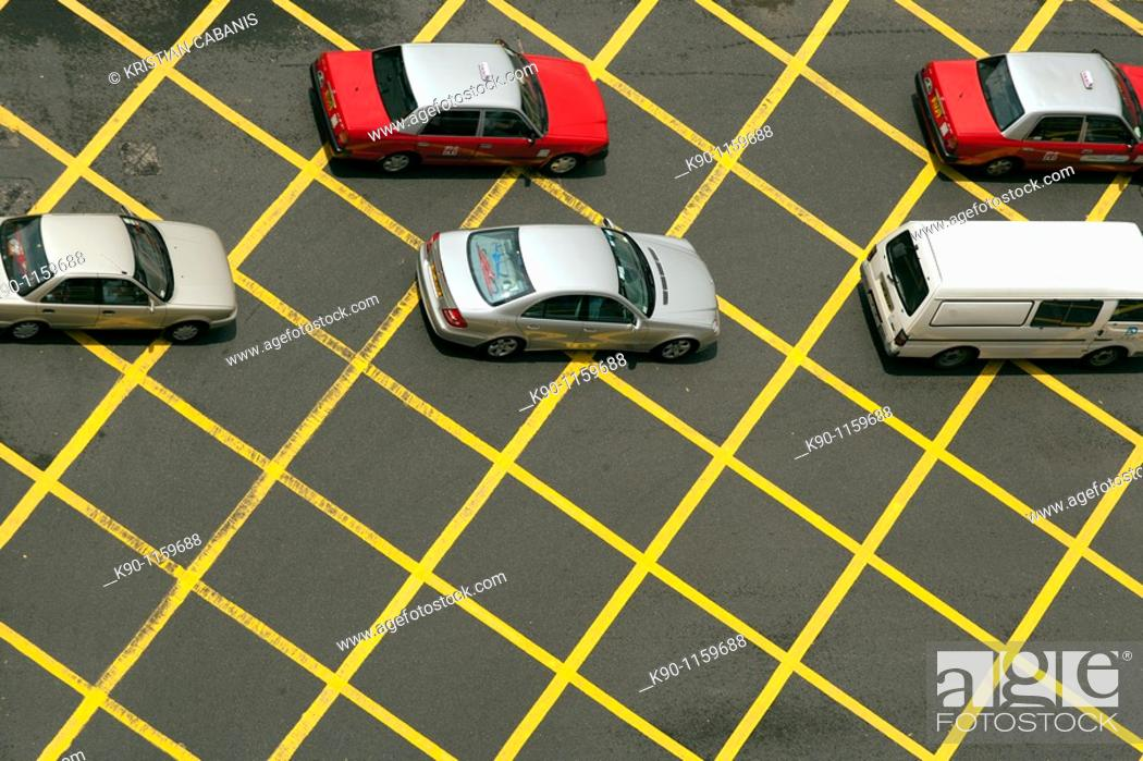 Stock Photo: Two taxis and three private cars seen from above standing in line while crossing a yellow grid of an intersection. Hong Kong, China.