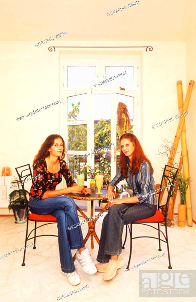 Stock Photo: Portrait of two young women seated at a table.