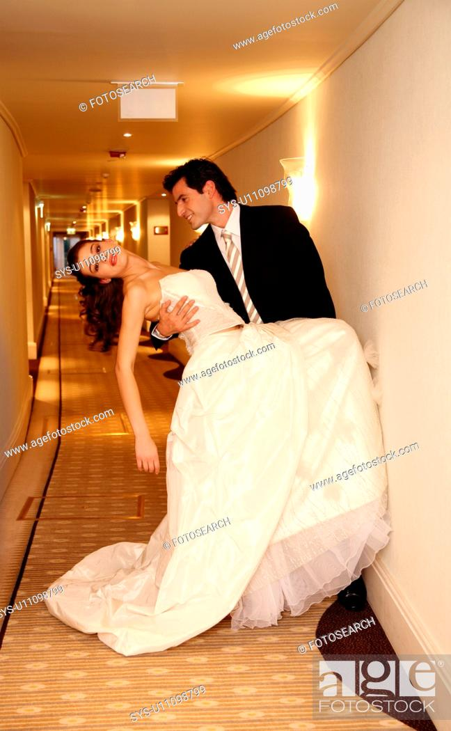 Stock Photo: Groom carrying bride into hotel room.