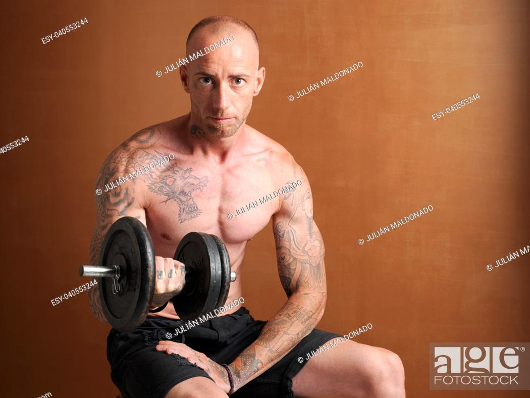 Stock Photo: Young bodybuilder lifting weights.