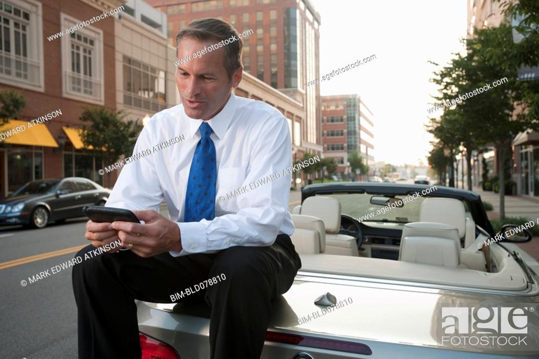Stock Photo: Caucasian businessman sitting on car text messaging on cell phone.