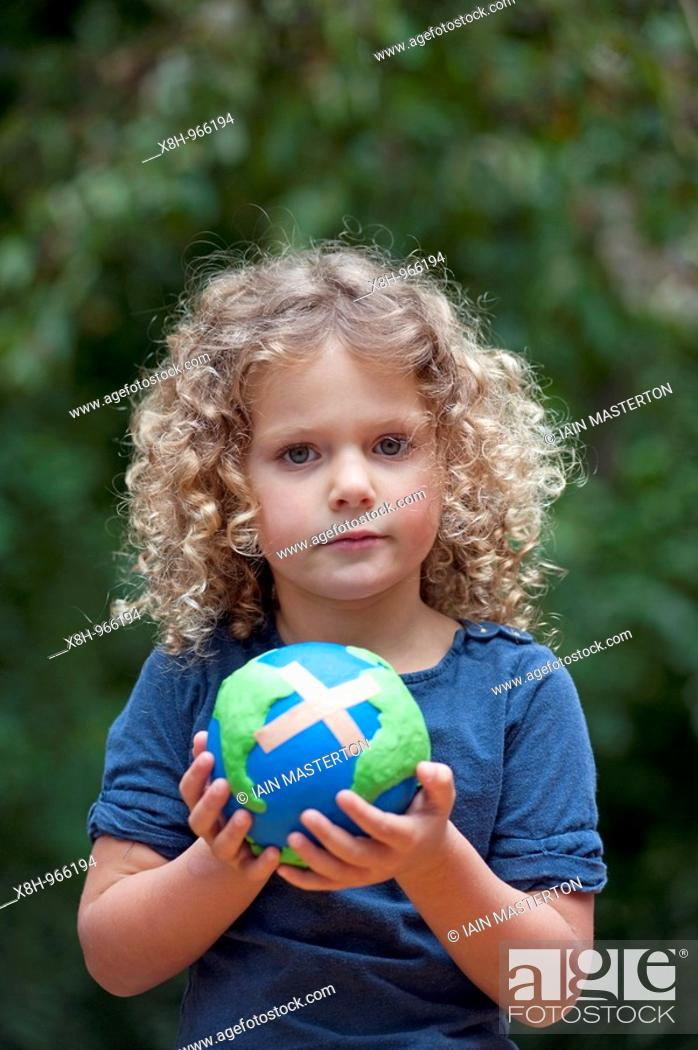 Stock Photo: young girl holding a model of a sick planet Earth with a Band-aid stuck to it.