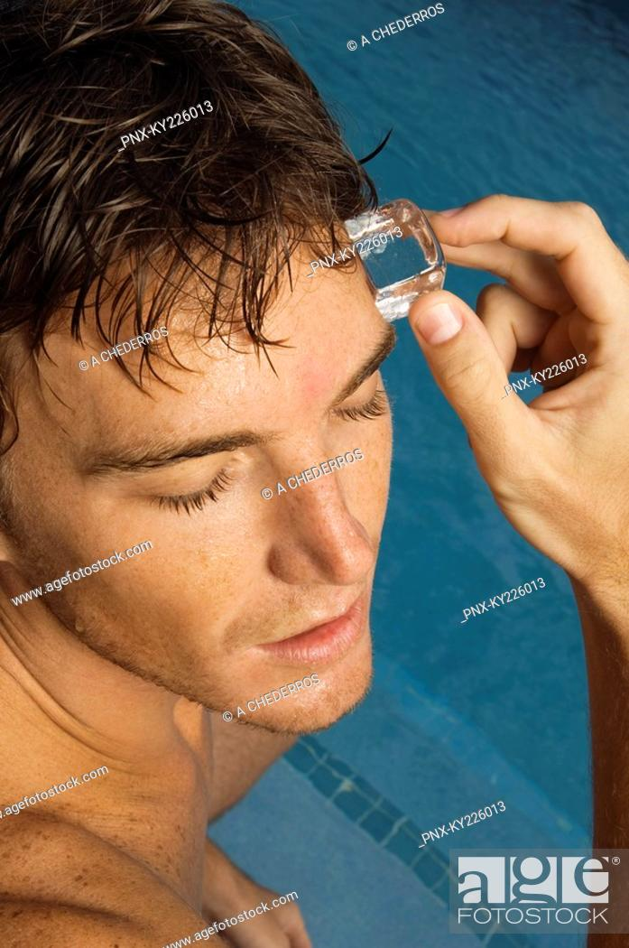 Stock Photo: Man rubbing an ice cube on his forehead.