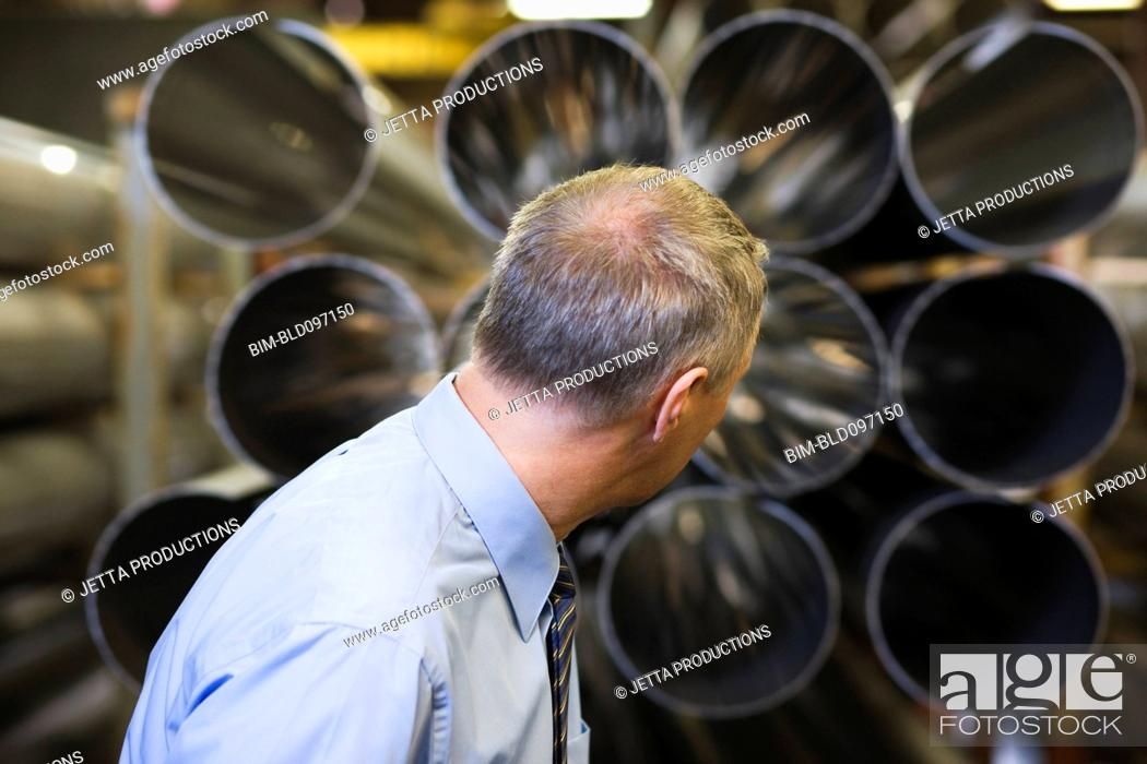 Stock Photo: Caucasian foreman looking at pipes in factory.