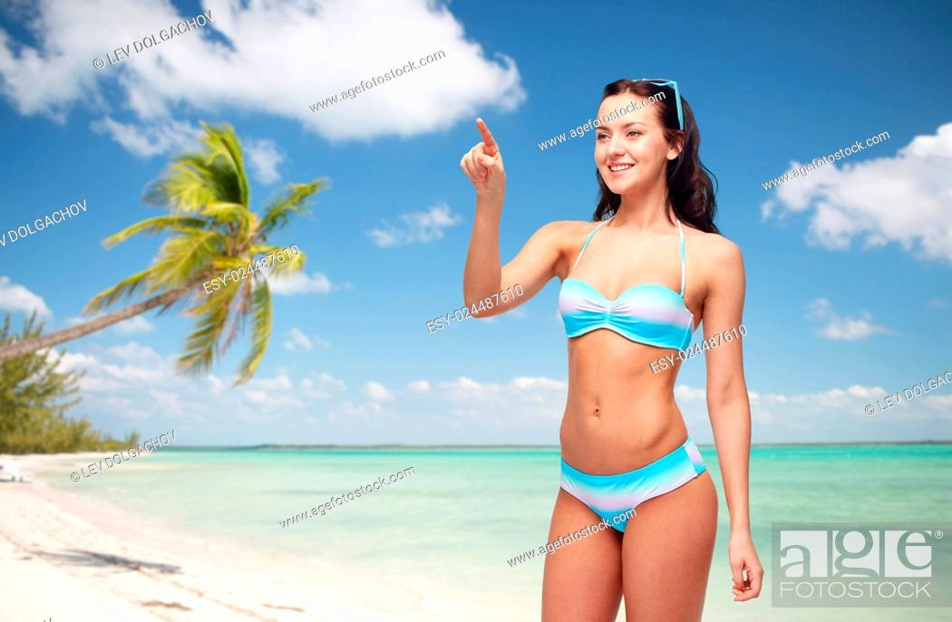 Imagen: people, travel, tourism, swimwear and summer holidays concept - happy young woman in bikini swimsuit pointing finger to something imaginary over exotic tropical.
