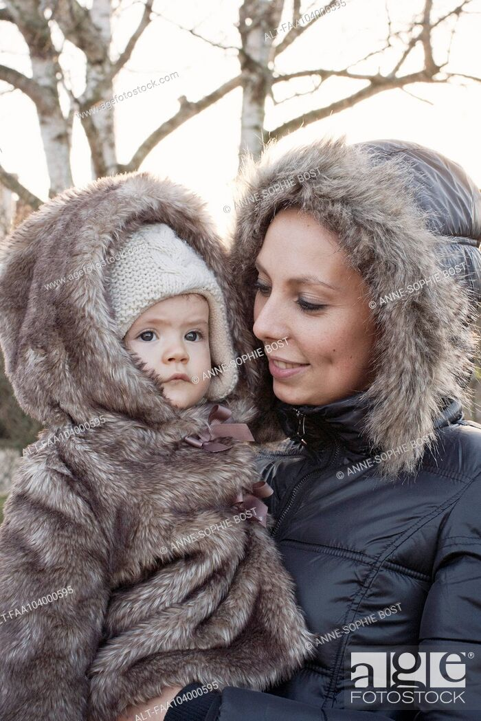 Stock Photo: Mother and baby girl dressed in winter coats, portrait.