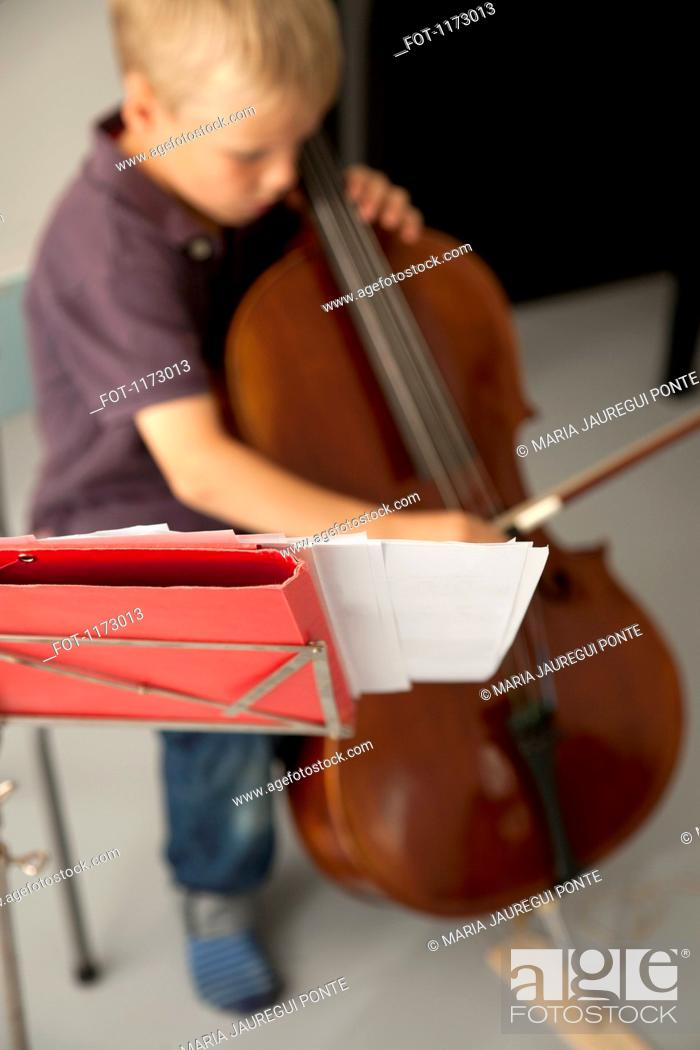 Stock Photo: Boy playing cello with sheet music in the foreground.