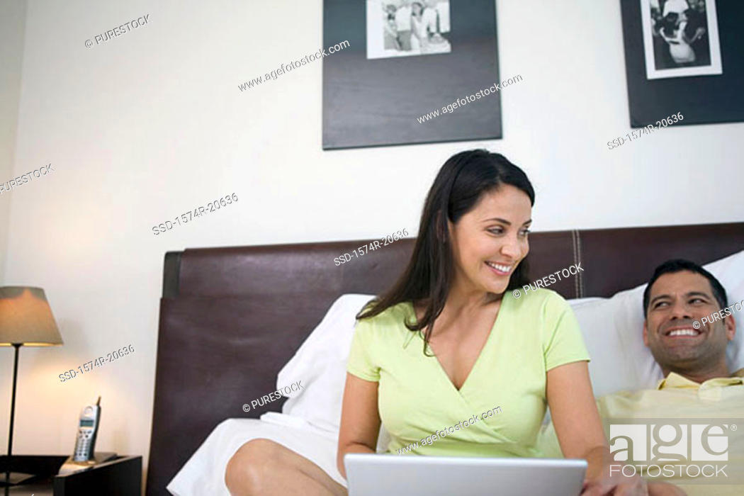 Stock Photo: Mature woman sitting in front of a laptop with a mature man lying beside her in the bed and smiling.