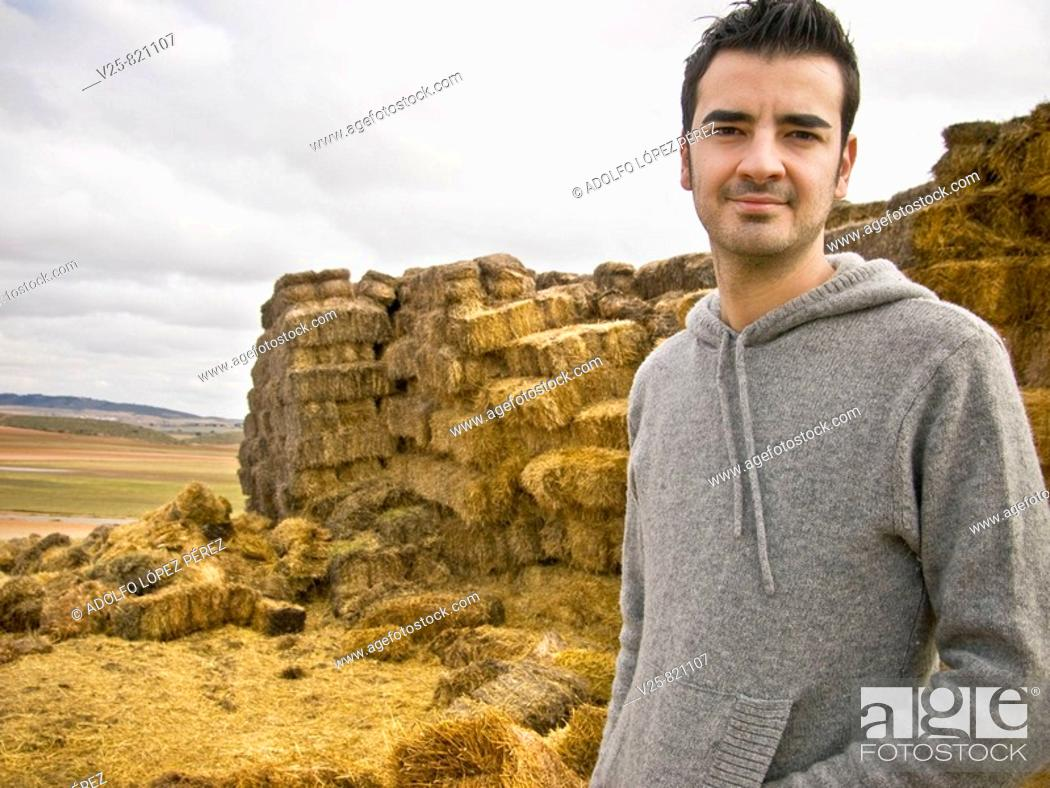 Stock Photo: Young shepherd, straw bales in background. Albacete province, Castile-La Mancha, Spain.