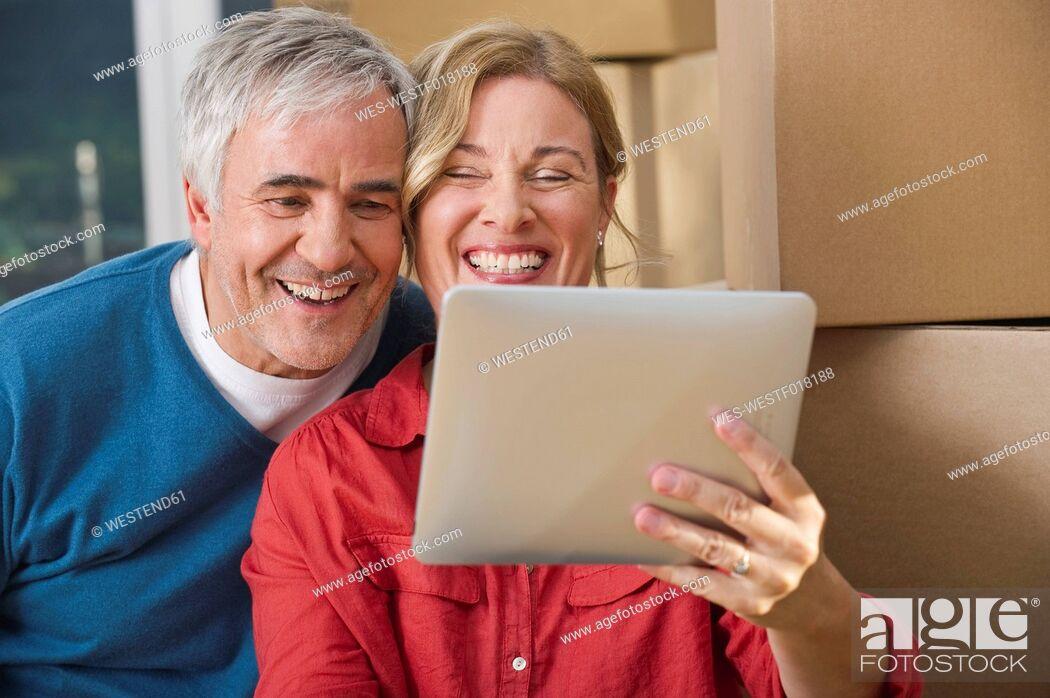 Imagen: Germany, Bavaria, Grobenzell, Couple using digital tablet, smiling.