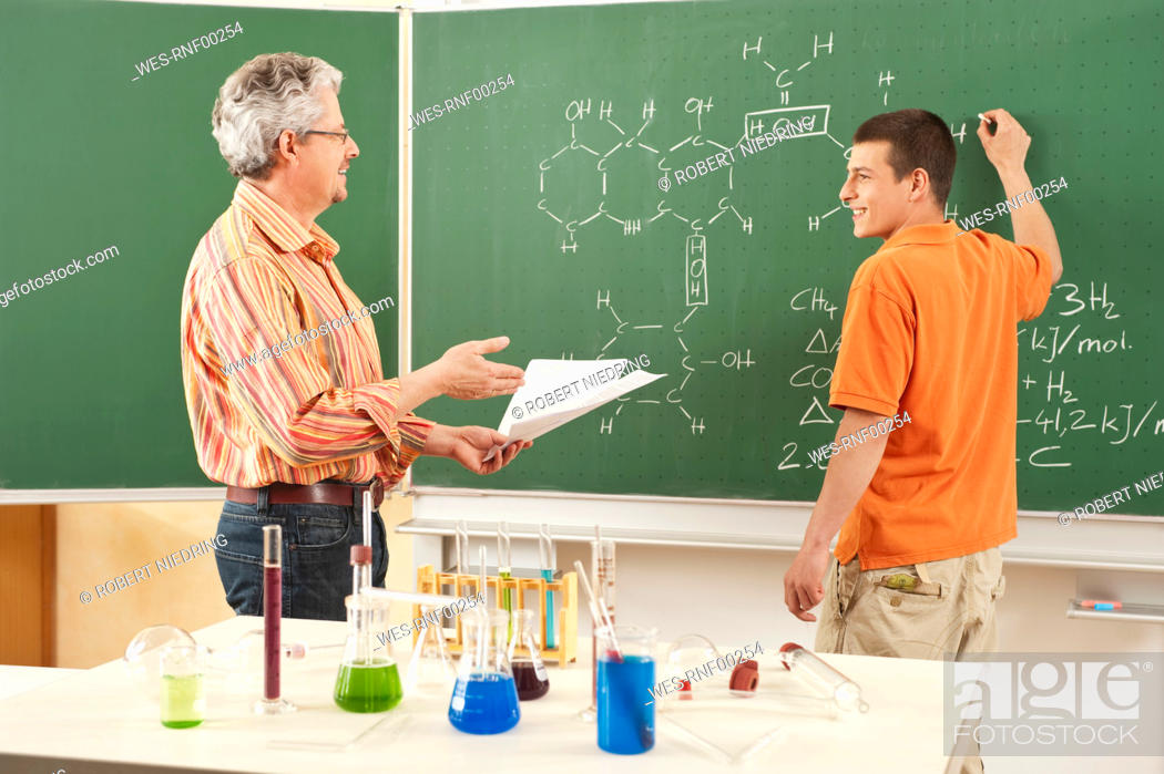 Stock Photo: Germany, Emmering, Young man solving problem on chalkboard, teacher standing beside.