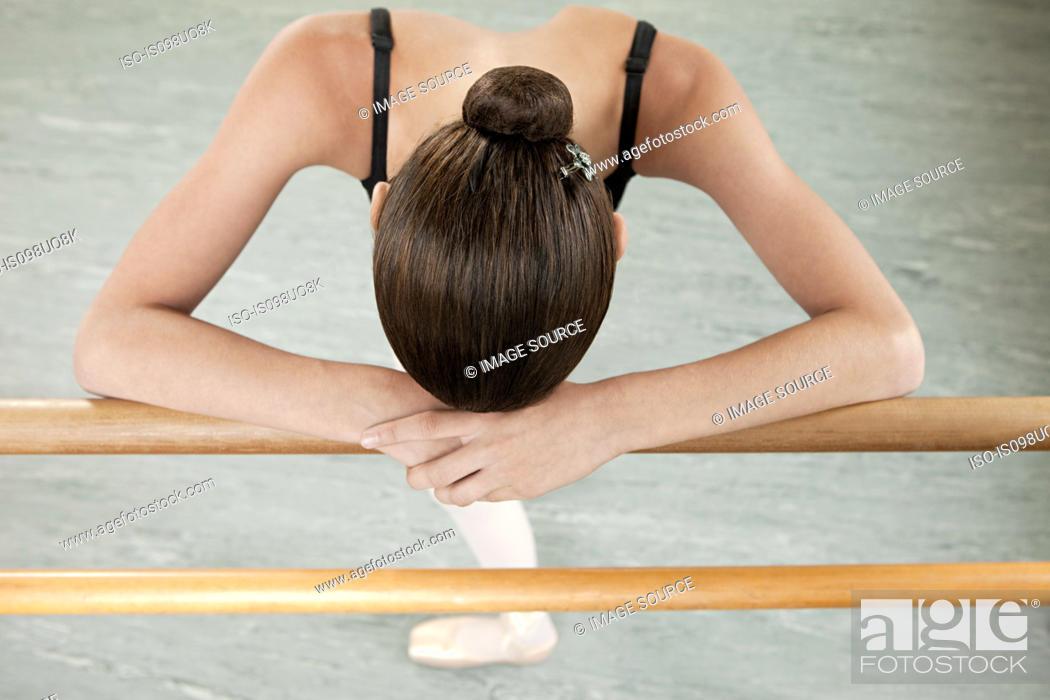 Stock Photo: Ballerina resting on barre.