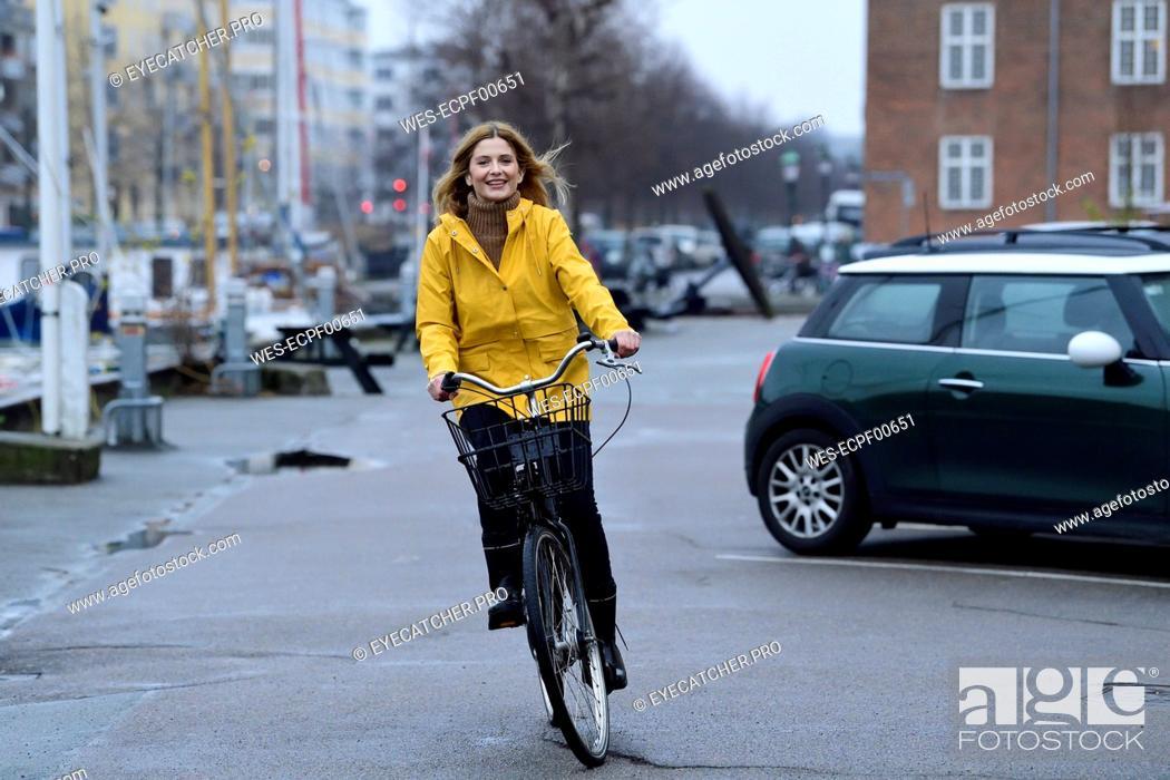 Stock Photo: Denmark, Copenhagen, happy woman riding bicycle on waterfront promenade in rainy weather.