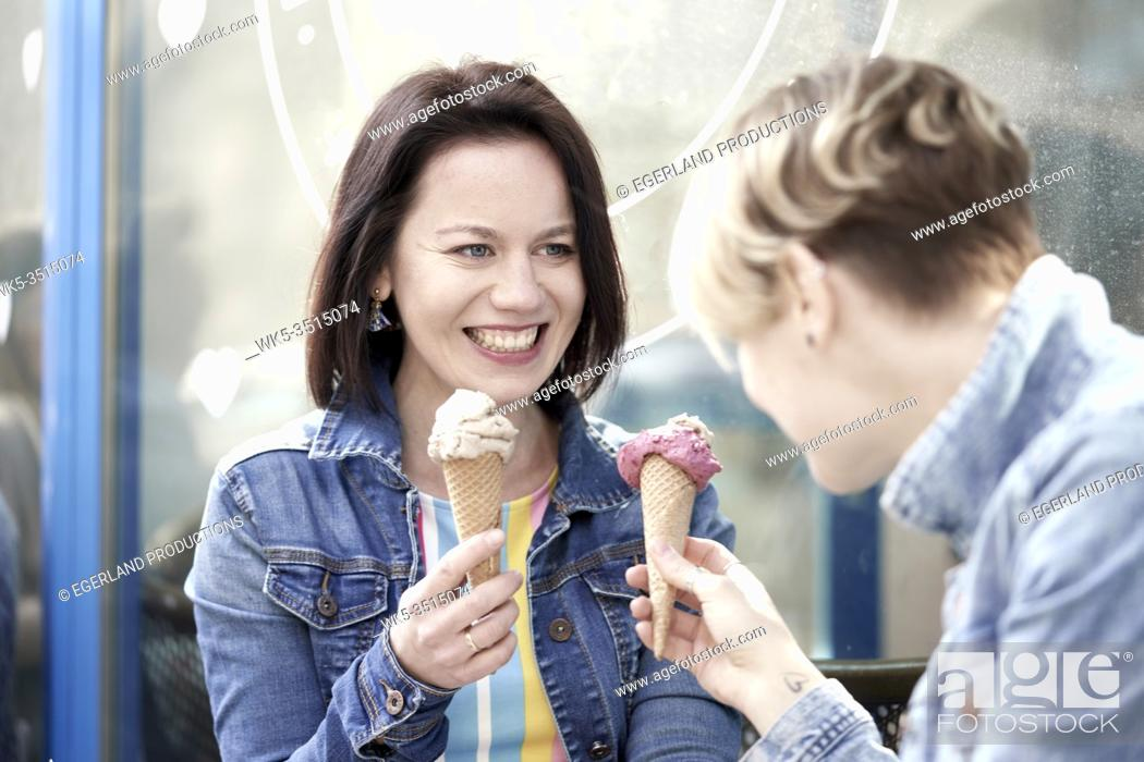 Photo de stock: Two happy female friends eating vegan dairy-free and sugar-free ice cream cone made with cashew nuts and dates.