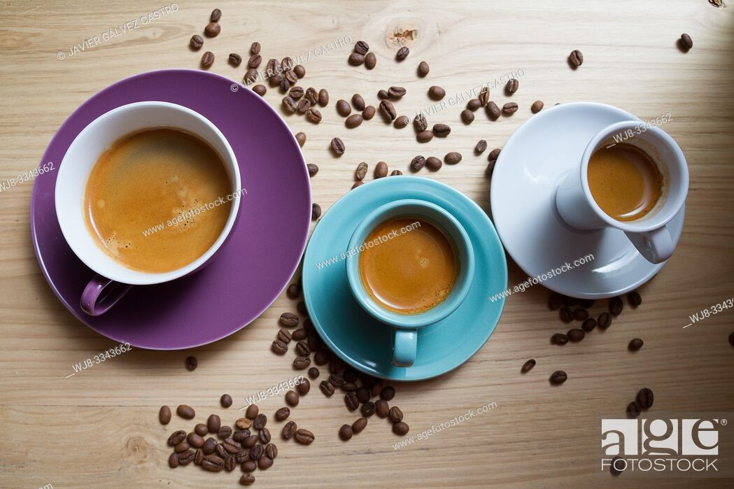 Stock Photo: White porcelain cups, cyan and magenta with expresso coffee, on wooden board decorated with roasted coffee beans.